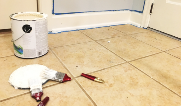 two paintbrushes against a tan tile floor, background includes wall with painters tape outline a freshly painted triam and molding.